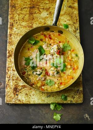 Spicy Red Lentil, Coconut, and Coriander Soup with Chicken Dumplings - Stock Photo