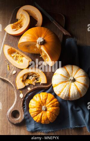 A piece of pumpkin on a wooden chopping board and munchkin pumpkins on a blue linen napkin - Stock Photo