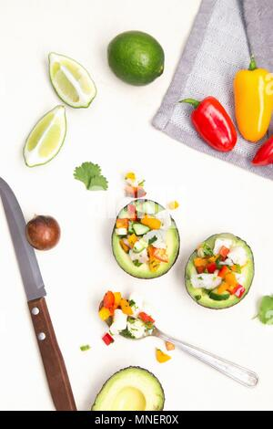 White fish ceviche with cucumber, peppers and coriander served in an avocado - Stock Photo
