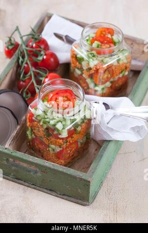 Bulgur wheat salad with pomegranate syrup, onions, cucumber, tomatoes, parsley and mint in a glass jar - Stock Photo