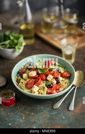 Rosemary pasta with fried tomatoes, feta and olives - Stock Photo