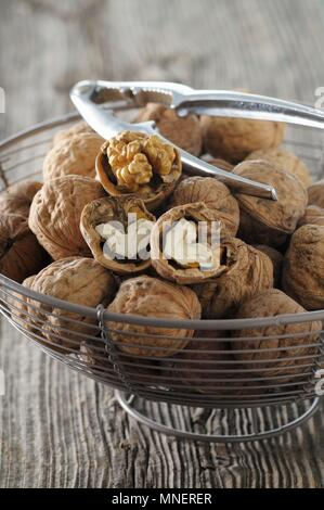 Walnuts with a nutcracker in a wire basket - Stock Photo