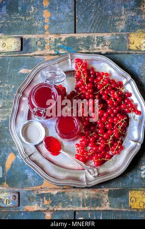 Redcurrant jam in glass jars on a metal plate - Stock Photo