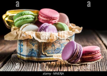 Colourful macaroons in an old metal tin - Stock Photo