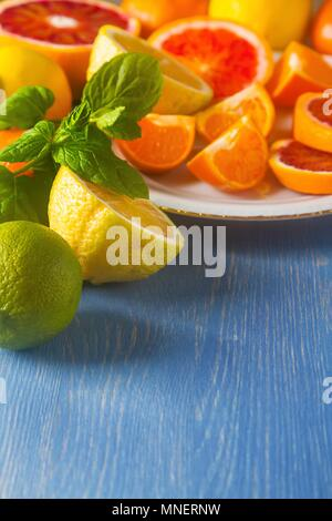 Assorted citrus fruit, whole and halved - Stock Photo