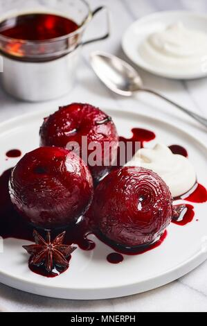 Plums poached in port wine with spices - Stock Photo