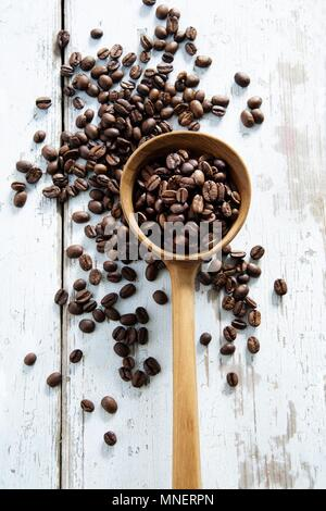 Coffee beans scattered on a table and in a wooden ladle - Stock Photo