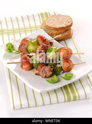 Sausages wrapped in bacon and Brussels sprouts on skewers - Stock Photo