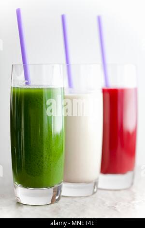 Three Assorted Smoothies in Glasses with Straws - Stock Photo