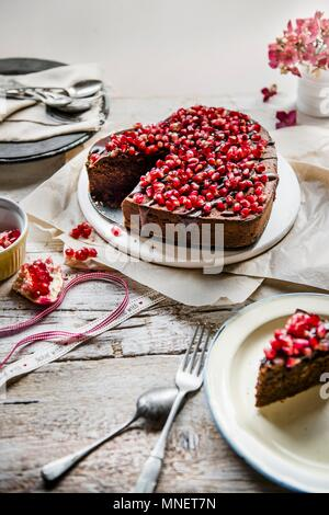 Chocolate cake in a shape of a heart with chocolate glaze and pomegranate seeds - Stock Photo