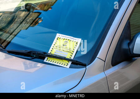 Parking penalty charge notice under car windshield wipers - Stock Photo