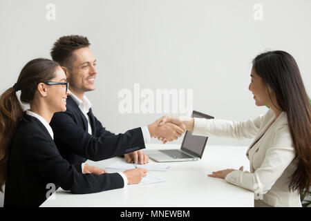 Smiling female applicant greeting HR managers with handshake - Stock Photo
