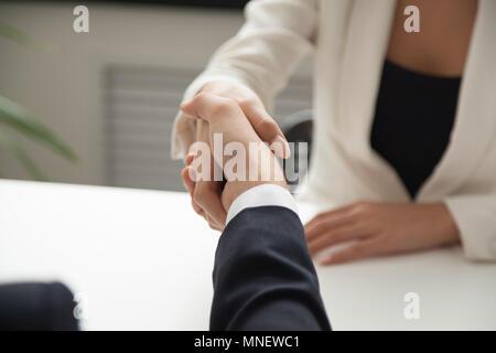 Female worker greeting business partner with handshake - Stock Photo