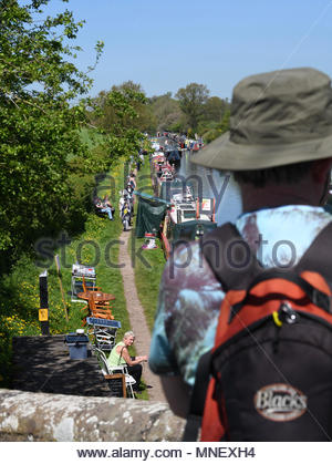 Looking over a man's shoulder, standing on bridge looking at narrowboats moored on a canal towpath. - Stock Photo