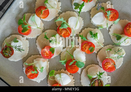 Mozzarella and tomatoes with thyme, arugula and Basil are on corn chips. Preparation of canapes. Close up. The view from the top - Stock Photo