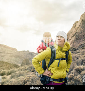 Superhero mother with little boy travelling in backpack. Hiking adventure with child on family trip in mountains. Vacations journey with infant carrie - Stock Photo