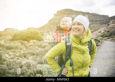 Super mom with baby boy travelling in backpack. Mother on hiking adventure with child, family trip in mountains. Vacations journey with infant carried - Stock Photo