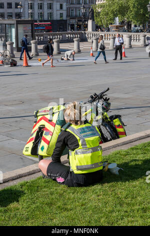 a cycle paramedic from the london ambulance metropolitan service sitting on the grass outside of the national gallery in trafalgar square in london. - Stock Photo