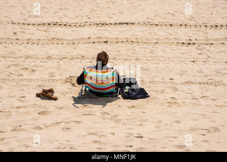 Spring Lake, NJ USA--May 15, 2018. A man in a lounge chair relaxes on the beach in Spring Lake, NJ. Editorial use only. - Stock Photo