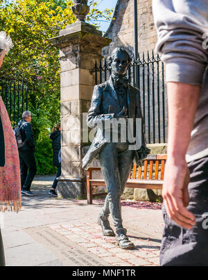 Bronze sculpture by David Annand of Robert Fergusson at Canongate Kirk , Royal Mile, Edinburgh, Scotland, UK with people passing by - Stock Photo