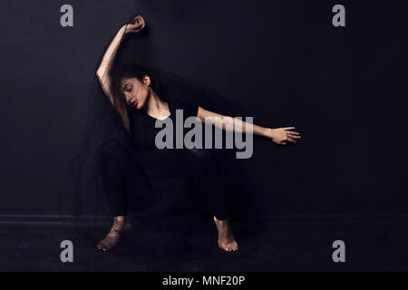 Portrait of young dancer sitting on floor on dark background ,Istanbul - Stock Photo