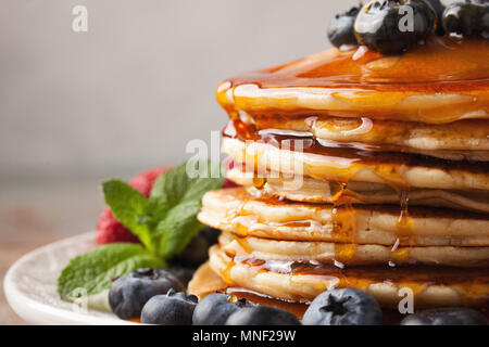 Close-up delicious pancakes, with fresh blueberries, strawberries and maple syrup on a light background. Sweet maple syrup flows from a stack of pancake - Stock Photo