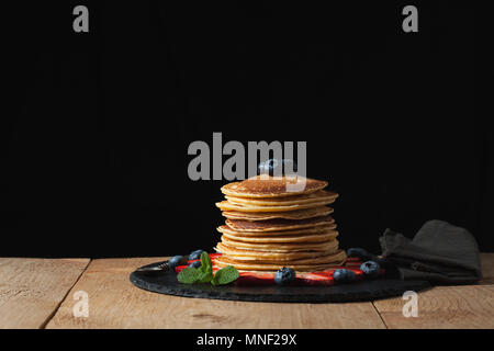 Front view of Stack of homemade plain pancakes with strawberries, blueberries and maple syrup served on black plate on black background with selective focus. With copy space - Stock Photo
