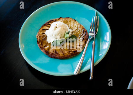 Apple tart with vanilla ice cream on dark background.Sweet delicious cake with ice cream and with caramel sauce.