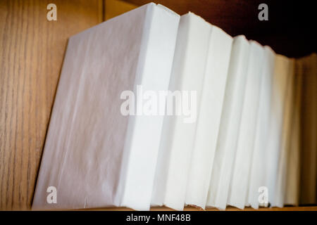 book shelf in the library, white cover book for fill your own texts.Book shelf with many books.a pile of books on wooden shelf. Selective focus. - Stock Photo