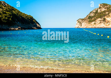 blue crystal water and white sand summer beach and holiday background with copy space.sandy beach in a bay at Paleokastritsa in Corfu, Greece - Stock Photo
