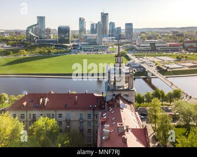 Scientists house tower stands in front of modern skyscrapers in oposide site of Neris river in Vilnius Lithuania in morning - Stock Photo