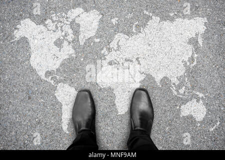 Businessman in black shoes standing on world map representing global business and business trip. - Stock Photo