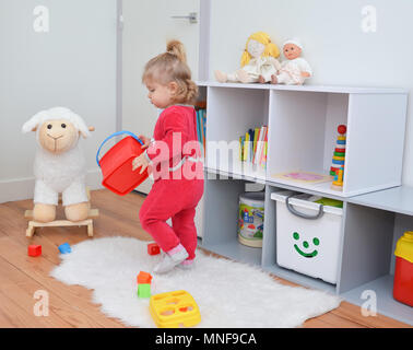 Girl playing with toys in the children's room - Stock Photo