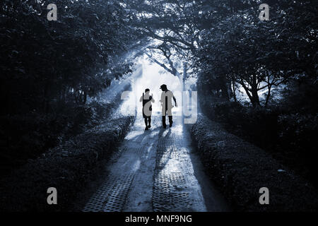 Silhouette two people walking and talking on the path through the forest as friends like they are walking to the paradise. Black and white monotone fi - Stock Photo
