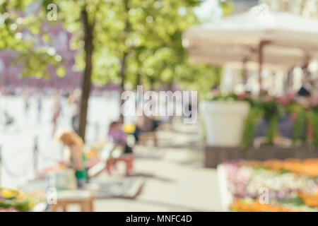 Abstract image of unrecognizable silhouettes of people walking in city street and resting on benches at sunny day. Urban modern background. Blurred effect - Stock Photo