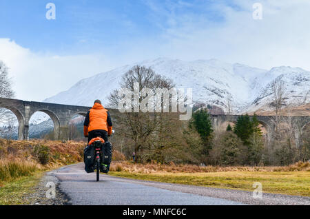 Man cycling (cycle touring) in front of Glenfinnan viaduct, Scotland - Stock Photo
