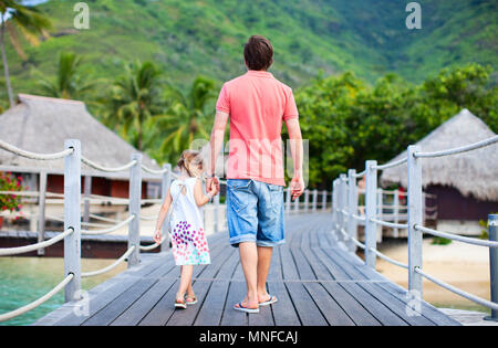 Back view of father and daughter at luxury tropical resort - Stock Photo