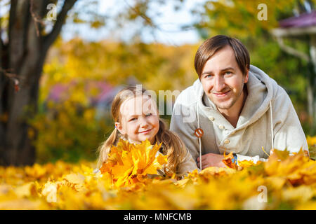 Father and his adorable little daughter outdoors on sunny autumn day laying on ground covered with fallen yellow leaves - Stock Photo