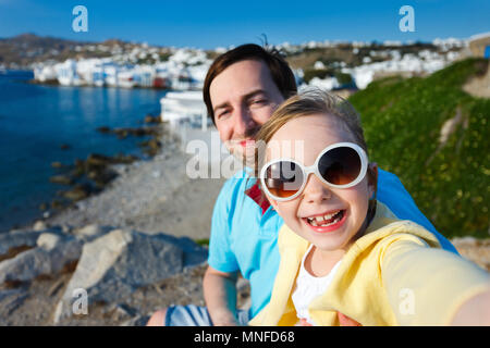 Happy family father and his adorable little daughter on vacation taking selfie at Little Venice area on Mykonos island, Greece - Stock Photo