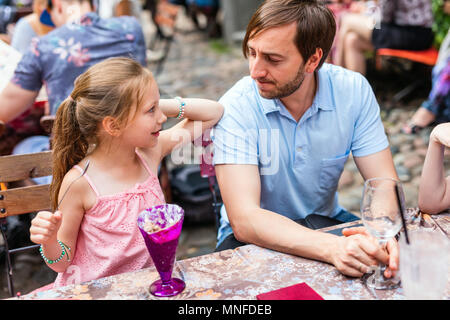 Father and his little daughter at outdoor cafe on summer day - Stock Photo