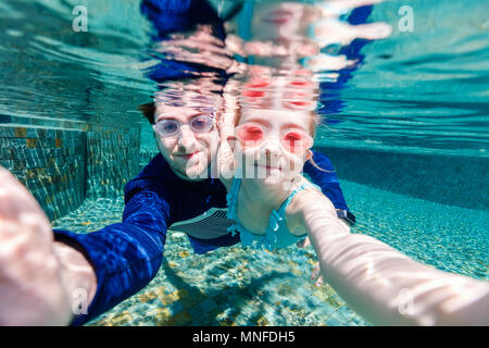 Family father and daughter swimming underwater and making selfie - Stock Photo