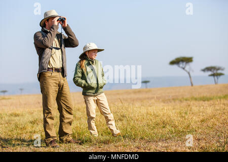 Family of father and child on African safari vacation enjoying bush view - Stock Photo