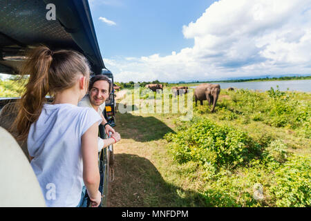 Family of father and daughter watching elephants at Udawalawe National Park in Sri Lanka - Stock Photo