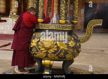Nuns lighting insense in front of prayer wheels, Yarchen Gar, Sichuan, China - Stock Photo