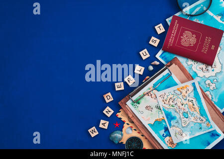 Sea travel and exploration concept. Watercolor maps, passport, compass, post envelopes, and Wanderlust wooden letters flat lay on a navy blue backgrou - Stock Photo
