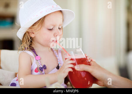 Casual portrait of adorable little girl drinking juice in outdoor restaurant - Stock Photo