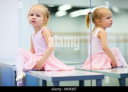 Adorable little ballerina wearing pink leotard in dancing school - Stock Photo