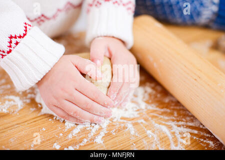 Close up of little girl kneading dough - Stock Photo