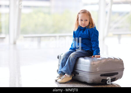 Adorable little girl at airport sitting on suitcase - Stock Photo