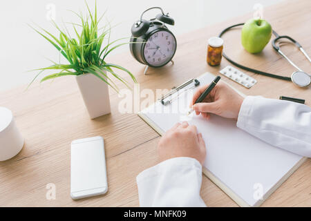 Female doctor writing notes, patient's medical history or medicine prescription on clipboard paper during medical exam in hospital office - Stock Photo